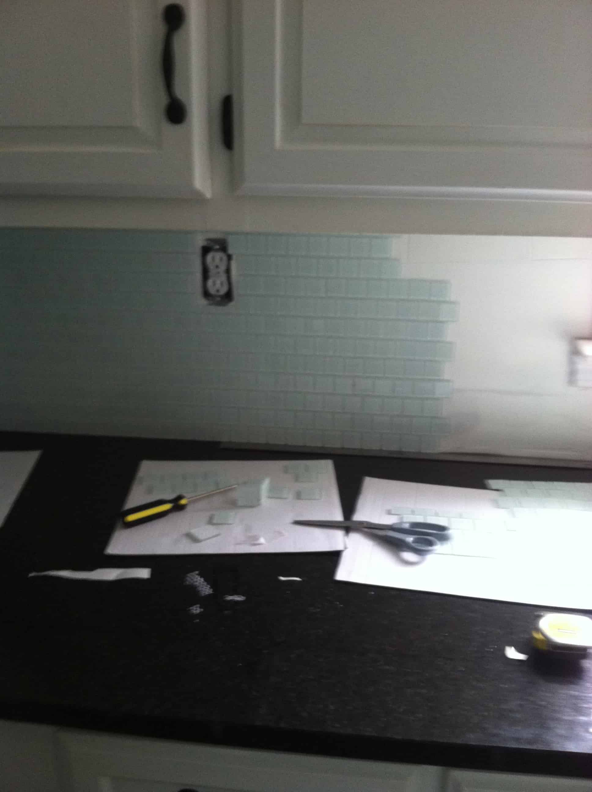 Glass tile sheets being cut to fit around a wall outlet during backsplash install