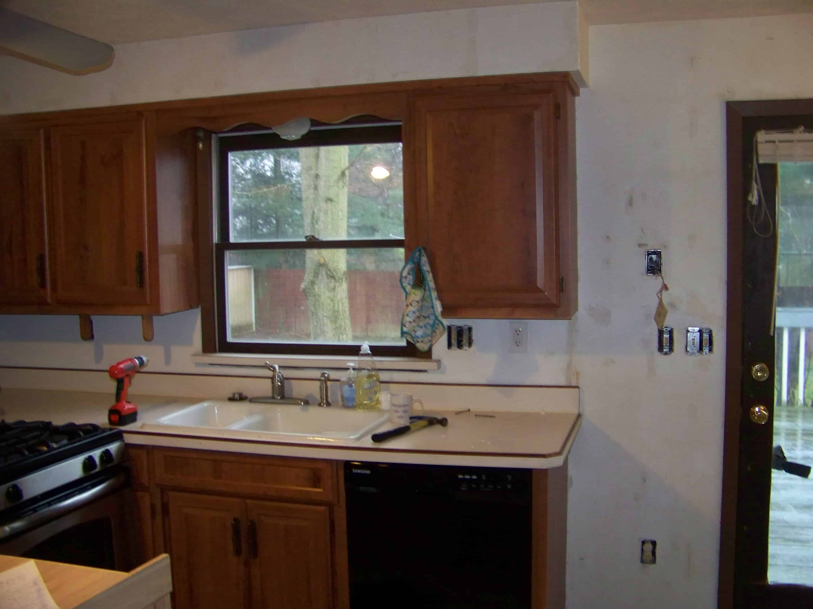 kitchen at the beginning of rennocation with old appliances and brown cabinets