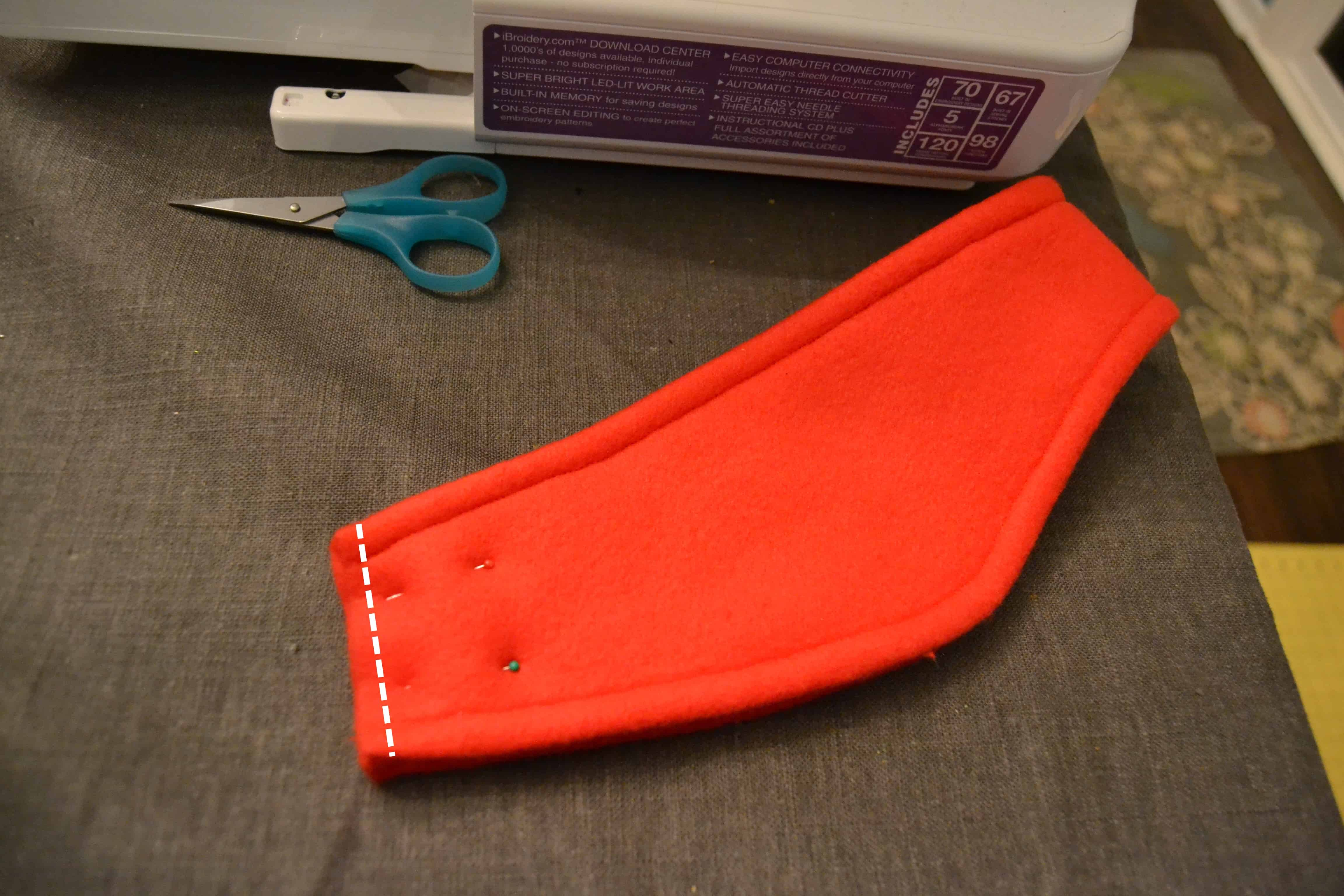 the headband folded in half and pinned at the open end with the two ends together and a line showing where to sew across to close the end