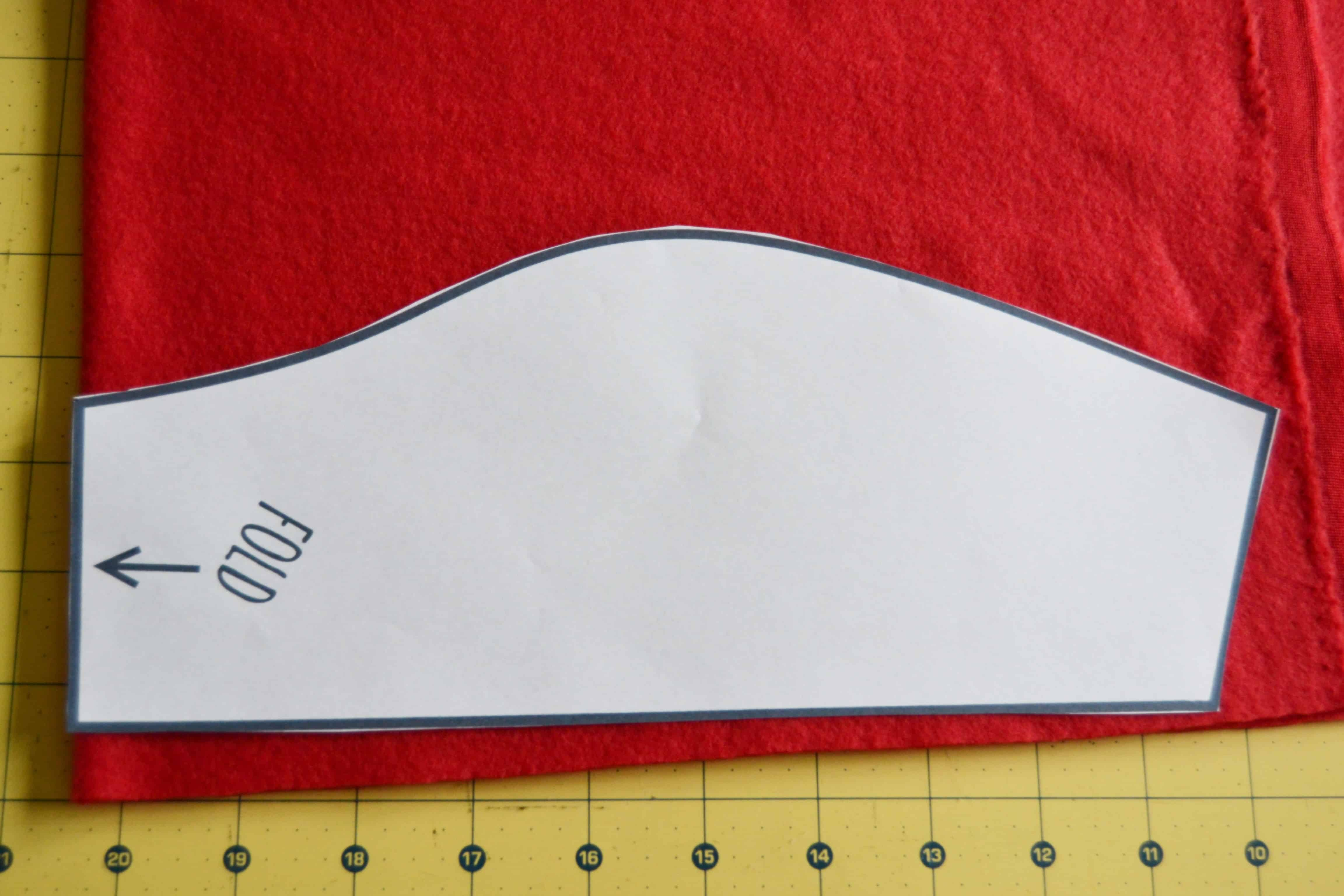 red fleece fabric laid out with the pattern laying on top