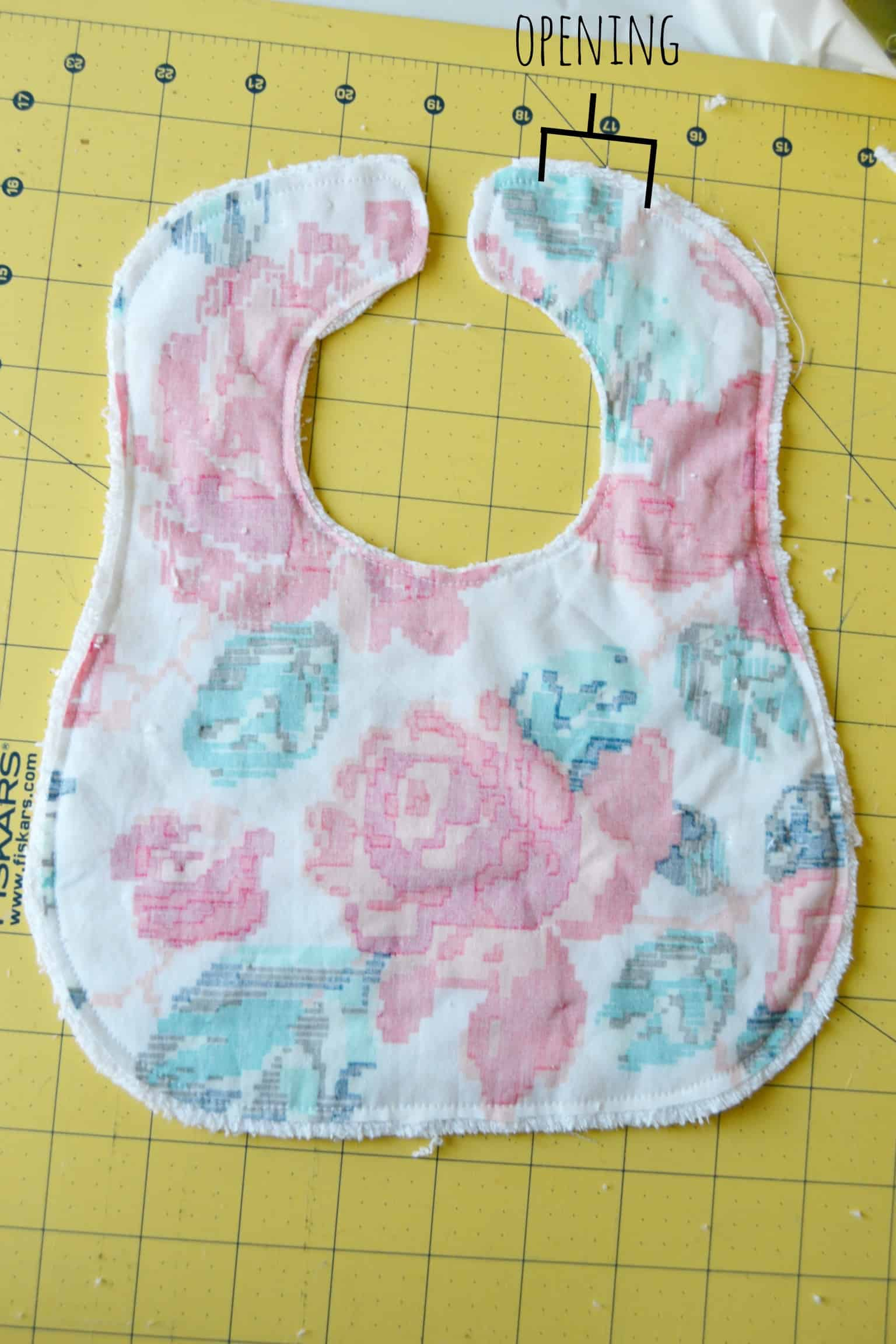 the two pieces of the baby bib sewn together with writing showing where the opening was left unsewn
