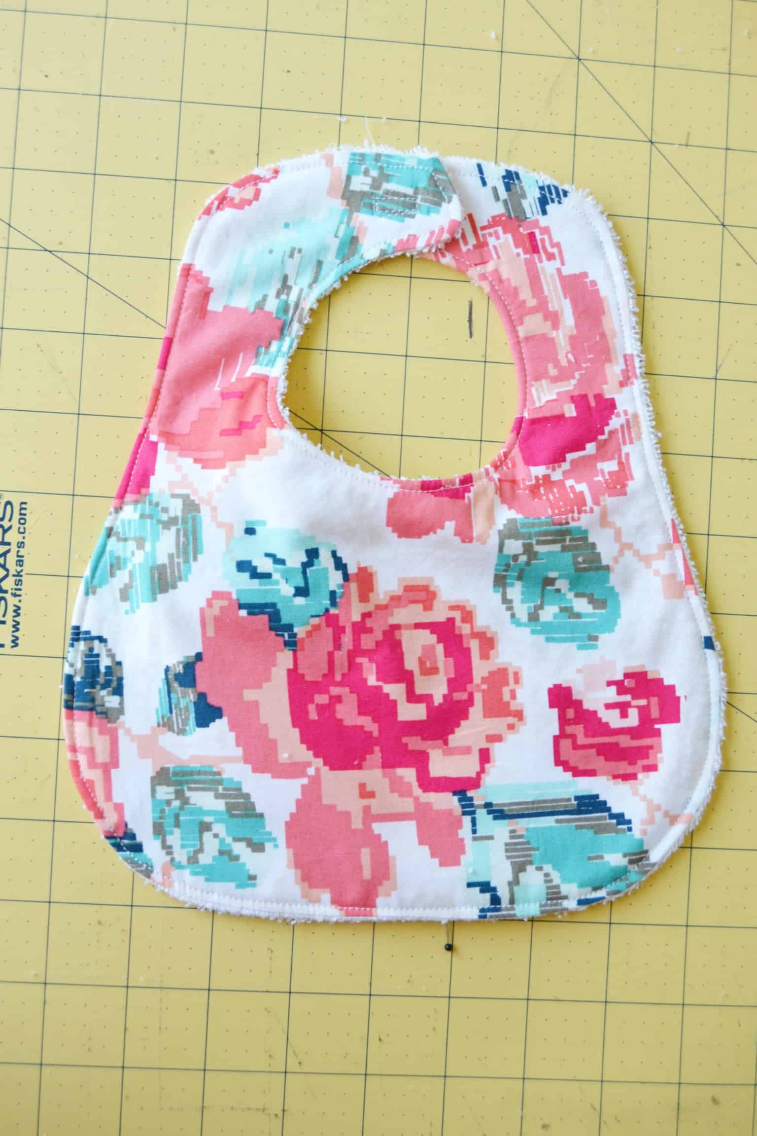 the finished bib showing where the velcro was sewn onto the straps