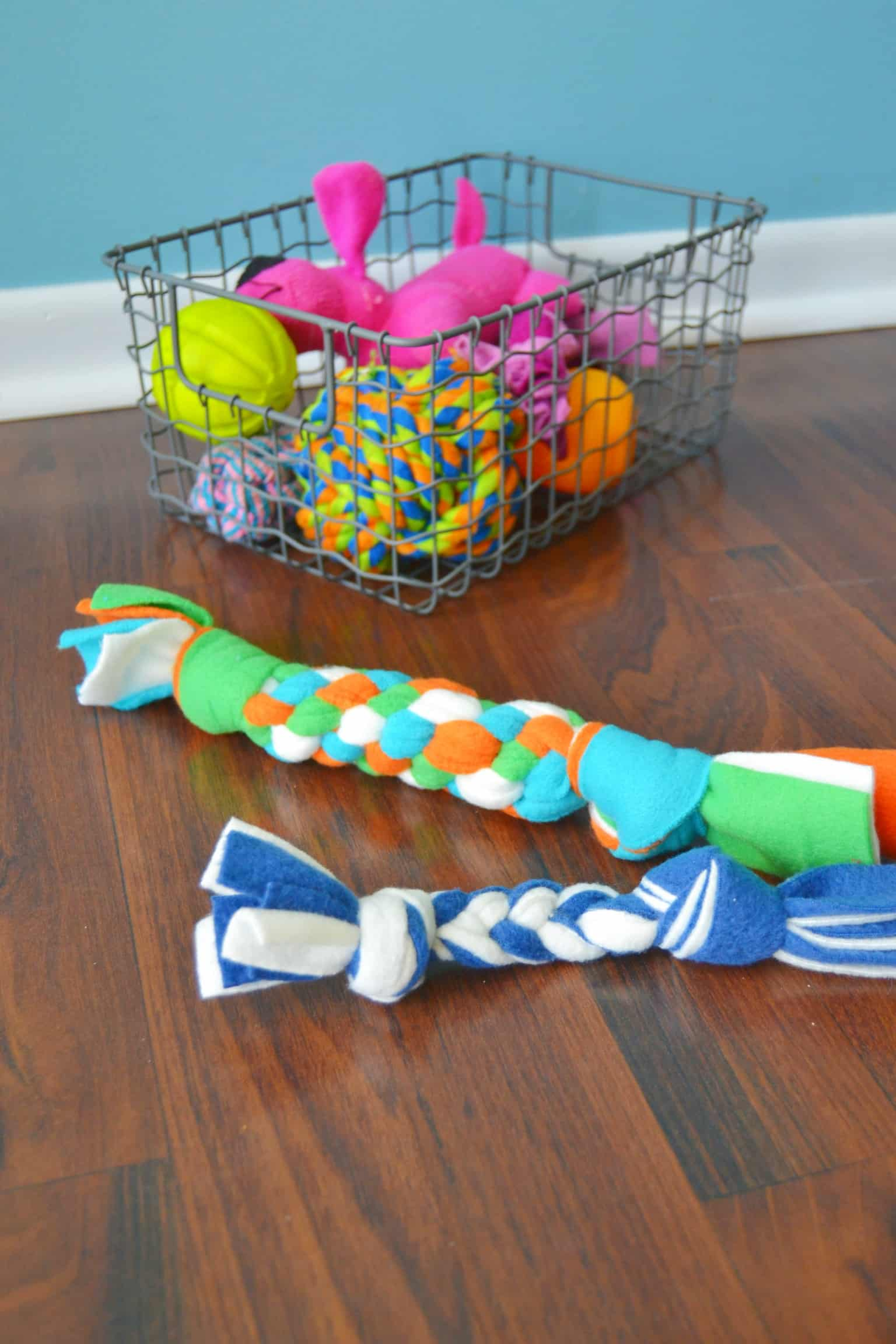 diy fleece dog toys in front of a basket of other dog toys
