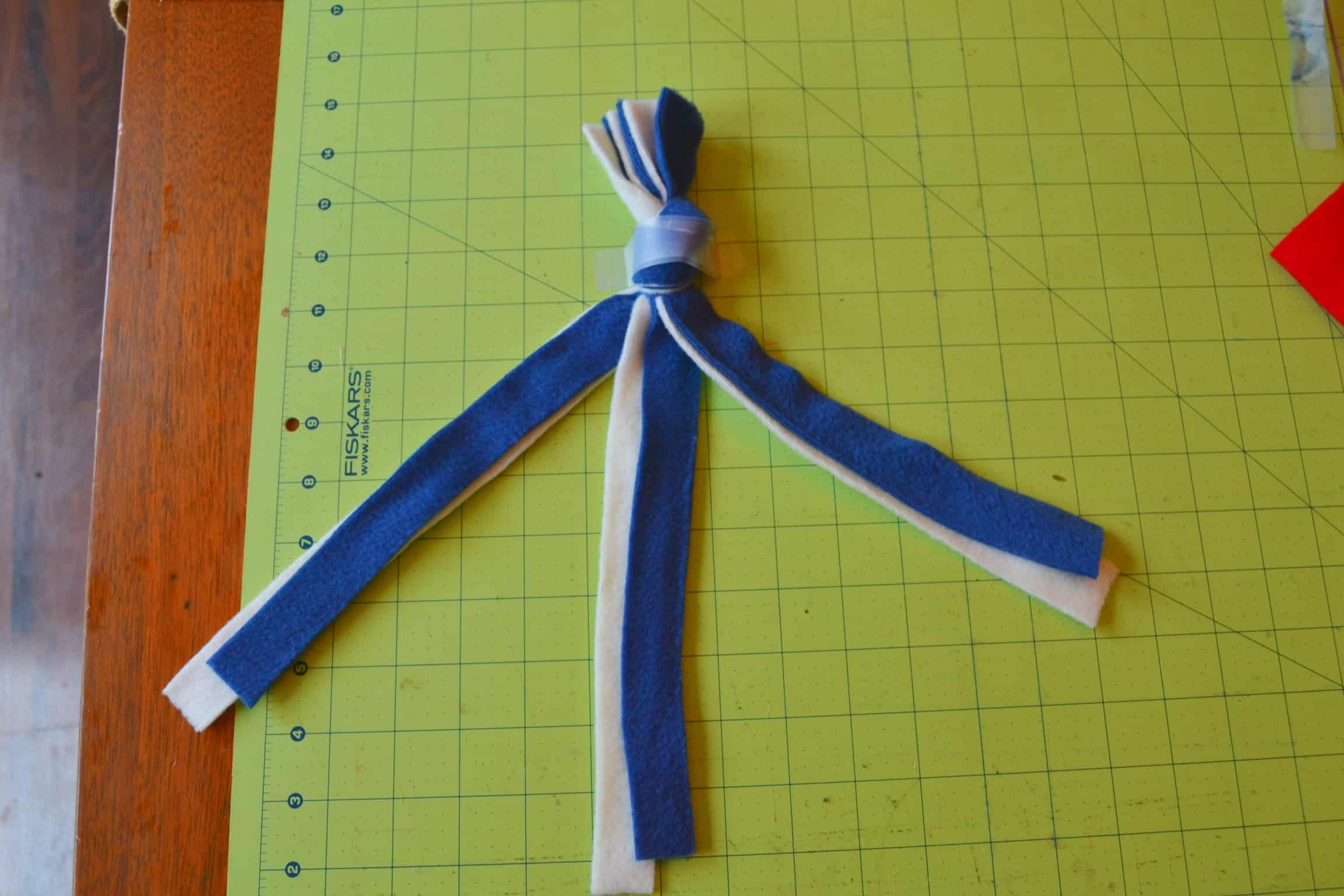 6 strips of fleece fabric with a knot at the top, separated into 3 groups of 2