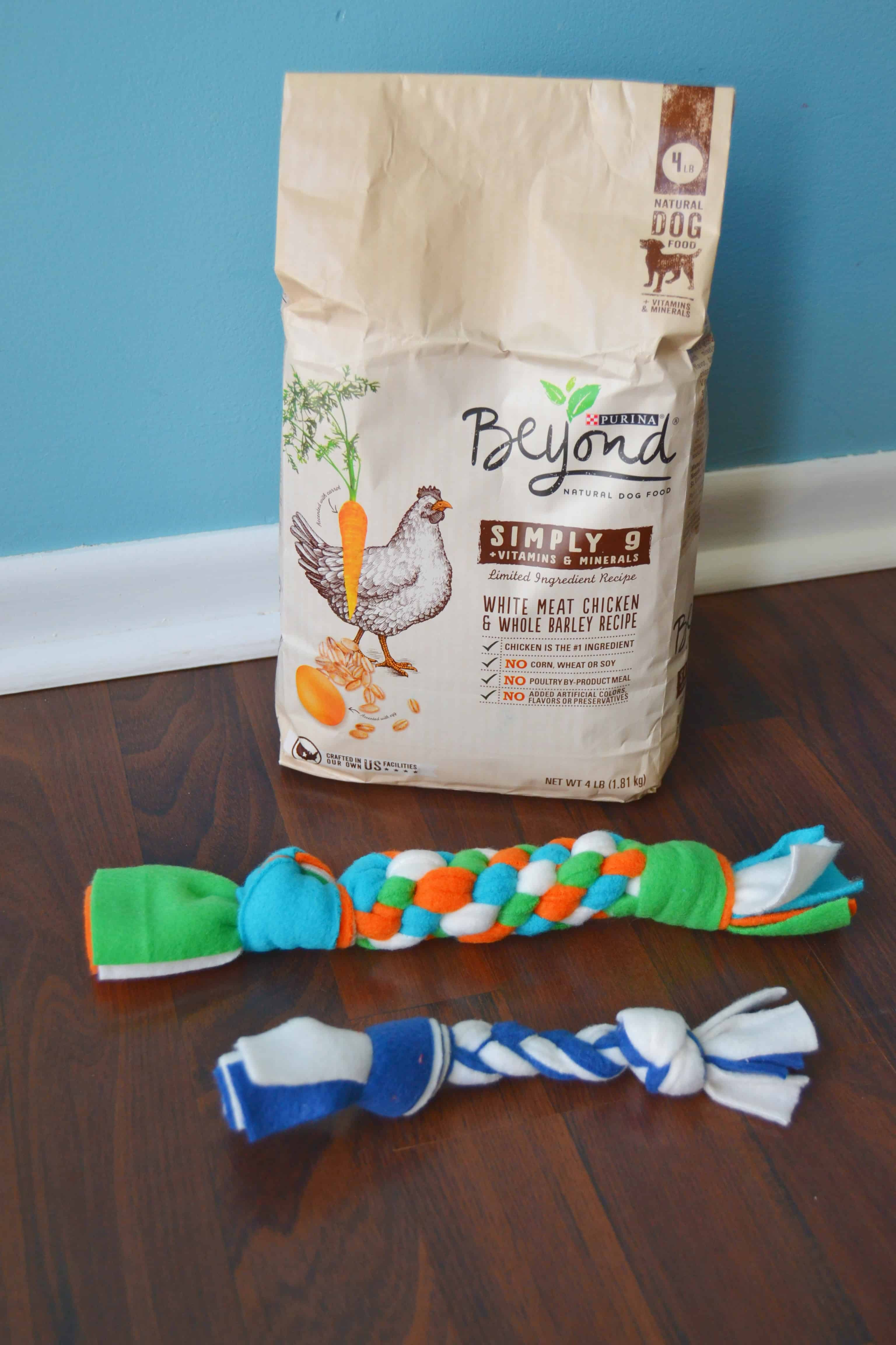 a bag of dog food with two homemade fleece dog toys in front of it