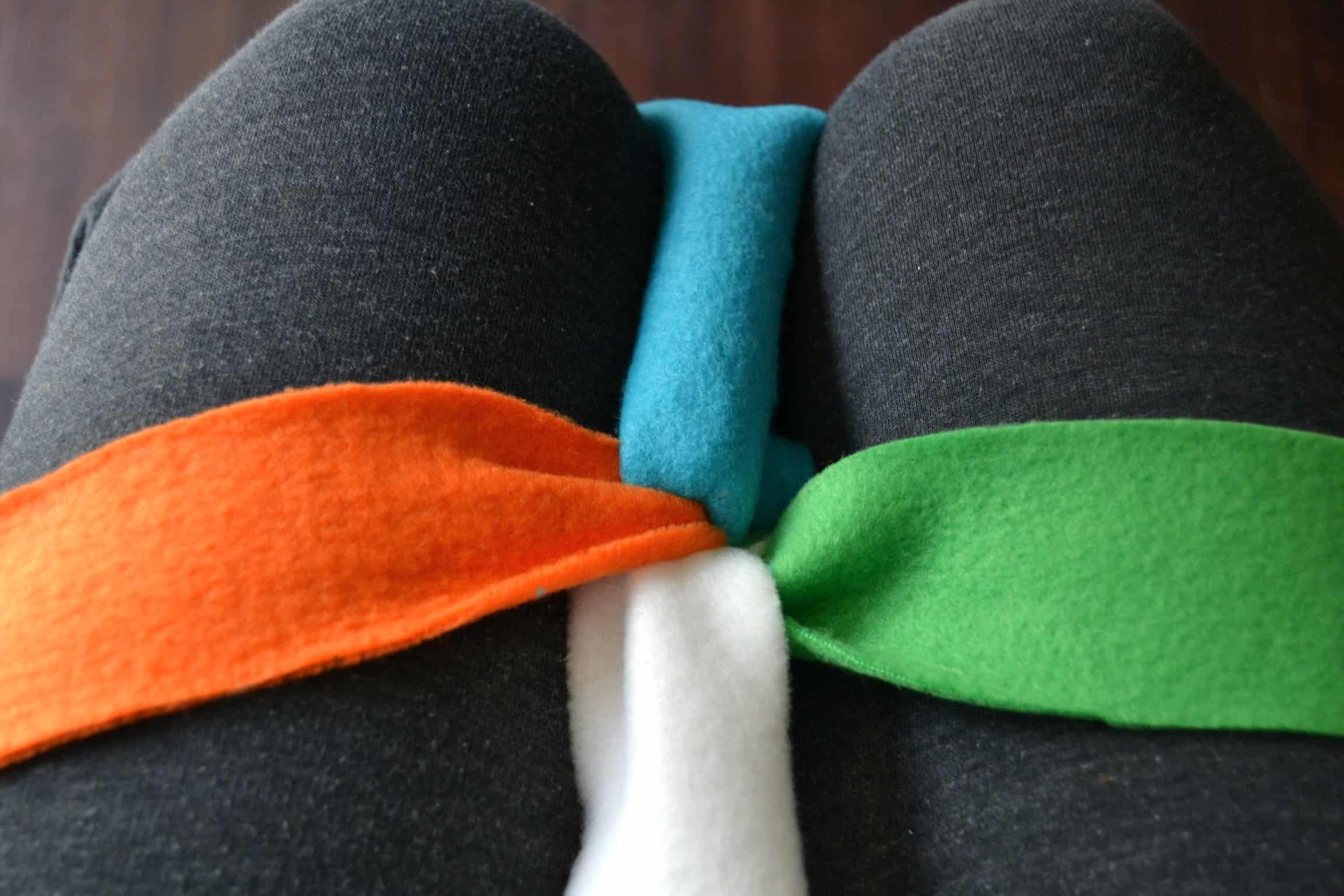 knot held into place between knees and 4 strips of fleece separated into a + shape