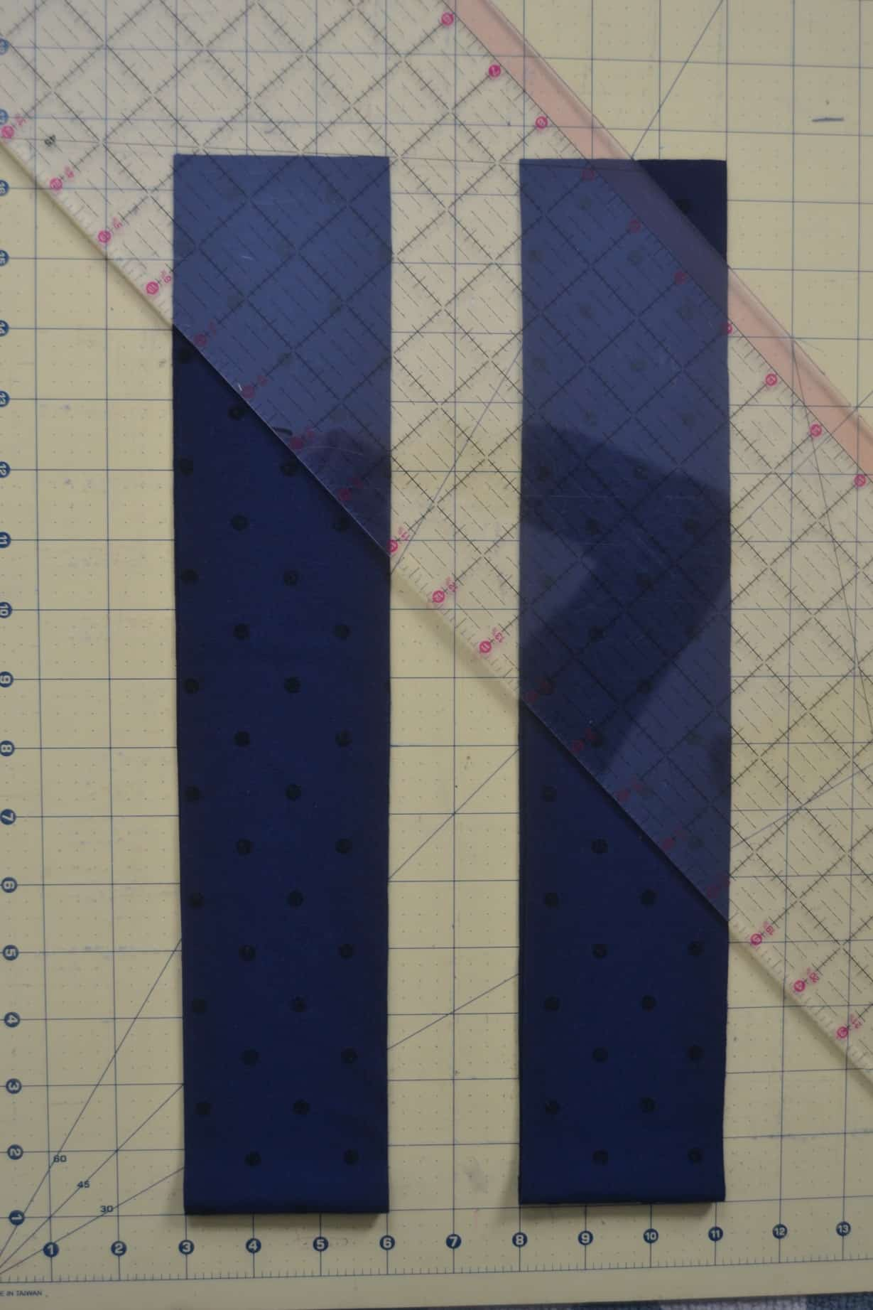 the two rectangles of fabric cut out and laid down on the cutting mat to have an angle cut into the ends