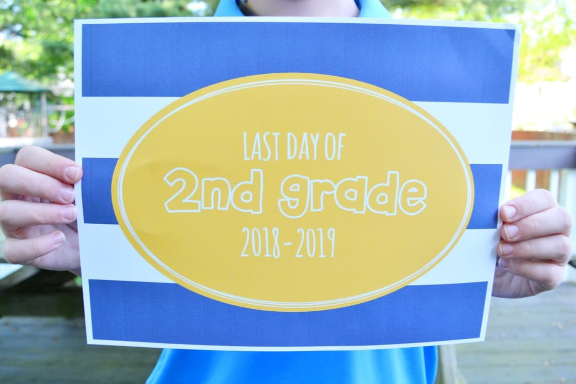 child holding a last day of 2nd grade sign