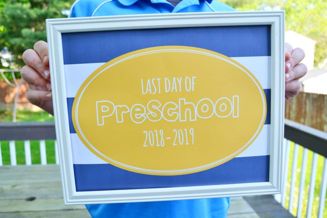 child holding a last day of preschool 2019 sign