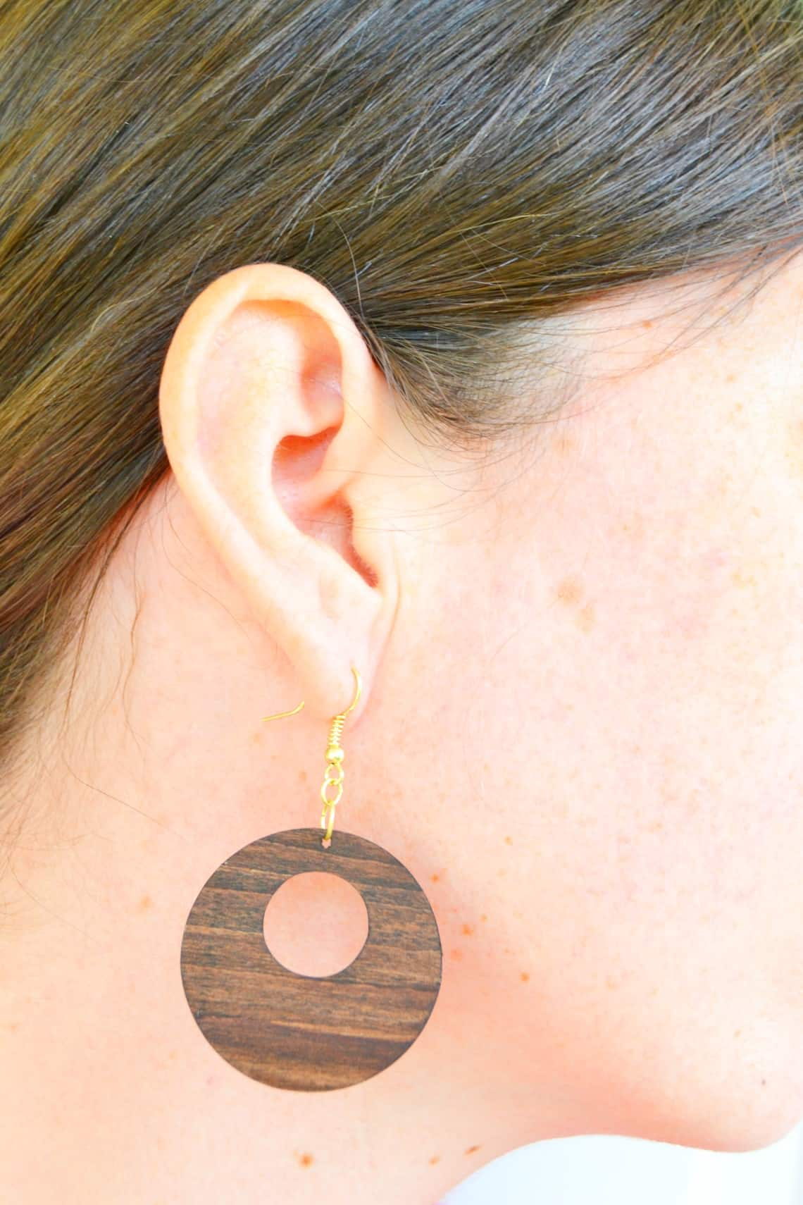 wooden earrings hanging from an ear