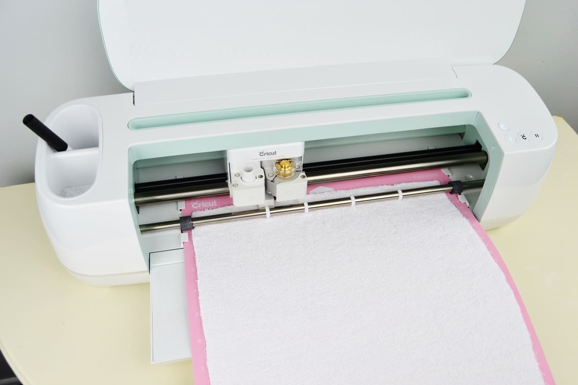The Cricut Maker cutting out the bib pattern piece from terrycloth