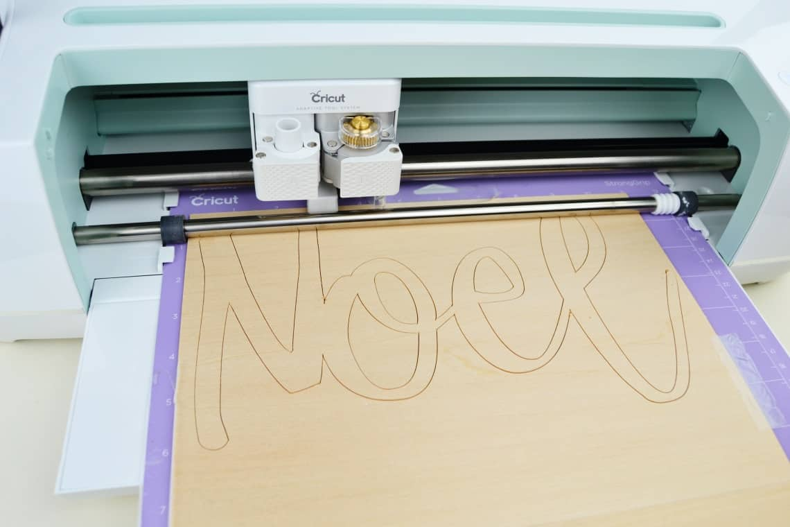 The Cricut Maker cutting out wooden letters during my trial for the Cricut Maker Review
