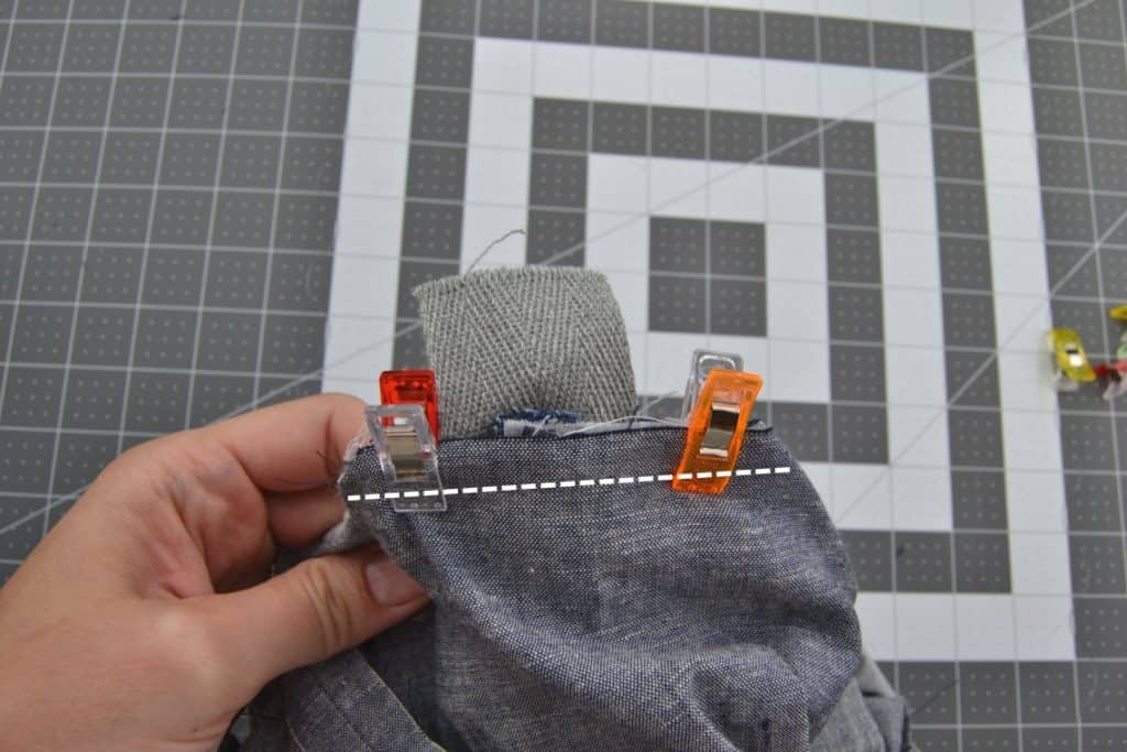 the corner with the lining, webbing, and outside fabrics all clipped together with a line showing where to sew