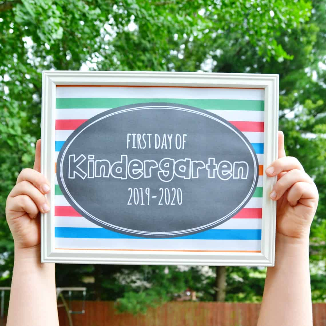 a printable first day of school signs 2019 framed and held in the air by a child