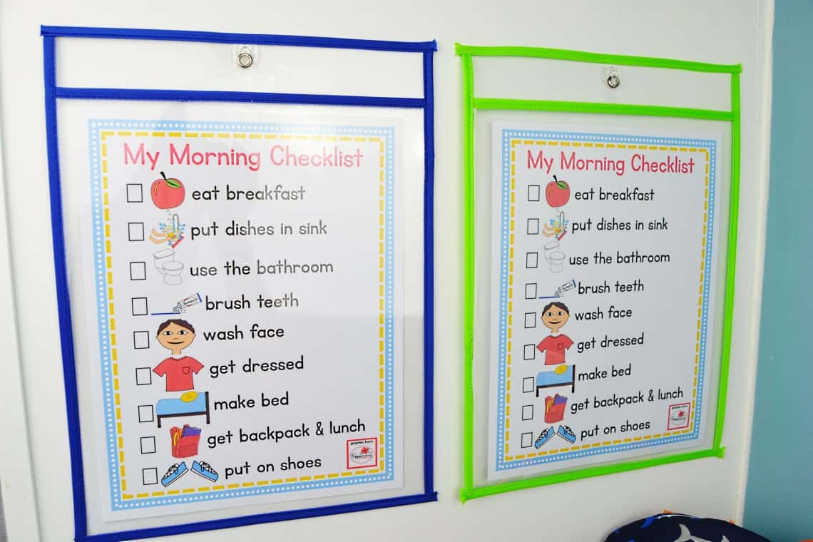 morning checklist for kids hanging on the side of the kitchen cabinet