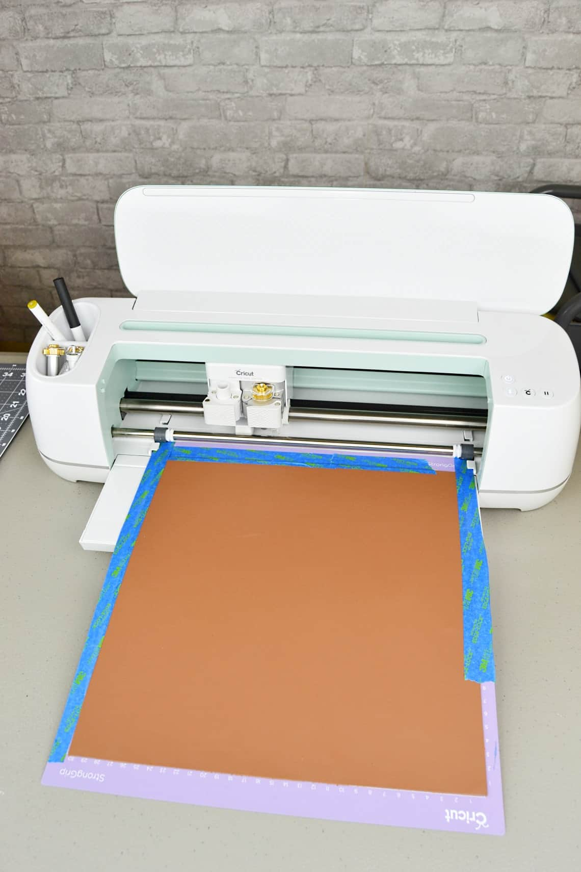the Cricut Maker with the leather sheet loaded onto the mat and ready to cut