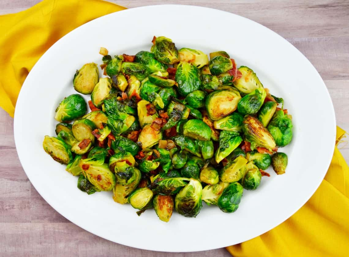 Pan Roasted Brussels Sprouts on a white platter with a yellow napkin