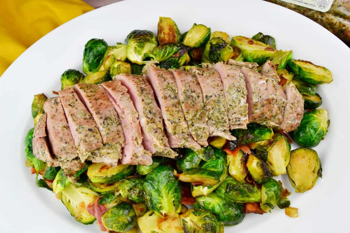 A close up of the pan roasted Brussels sprouts with the pork tenderloin on top