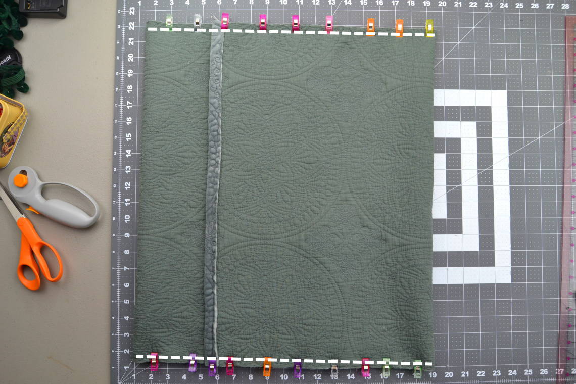 "the pillow cover fabric with both sides folded toward the middle and pinned along the ""long"" side with lines to show where to sew"
