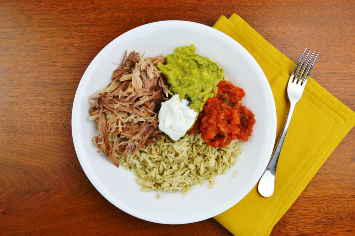 slow cooker carnitas shredded up and put together with ingredients to make a rice bowl