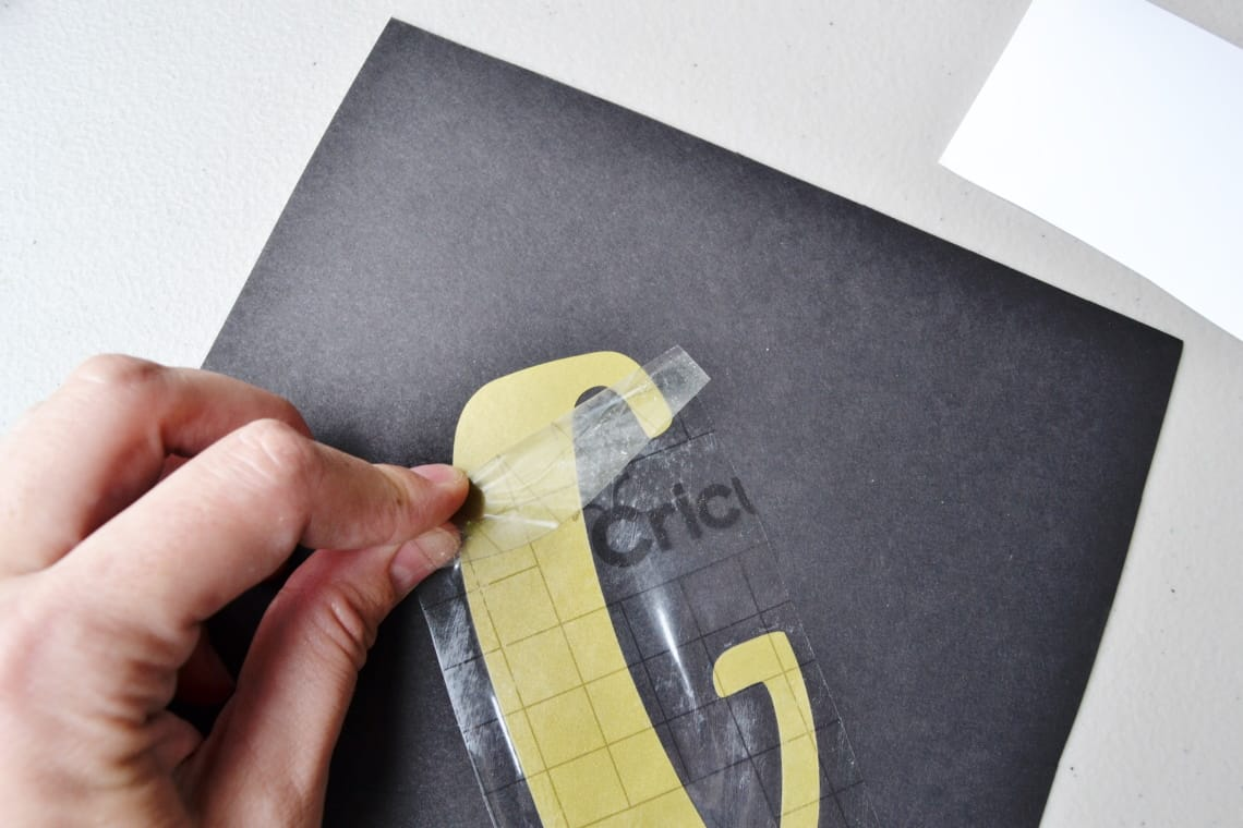 using the transfer tape to apply the vinyl to the paper for the banner