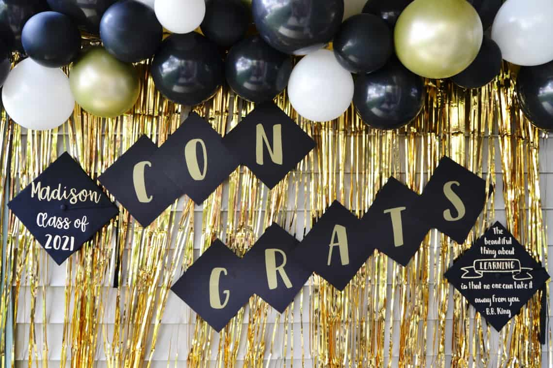 DIY Graduation party decorations with the completed Congrats banner and decorated graduation caps