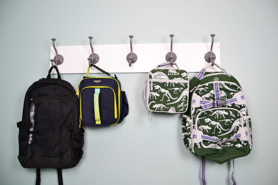 the mud room hook rack with book bags and lunch bags