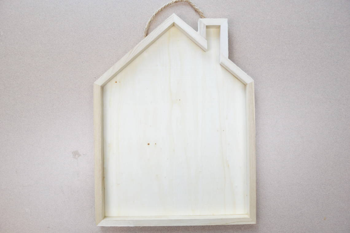 wooden sign shaped like a house